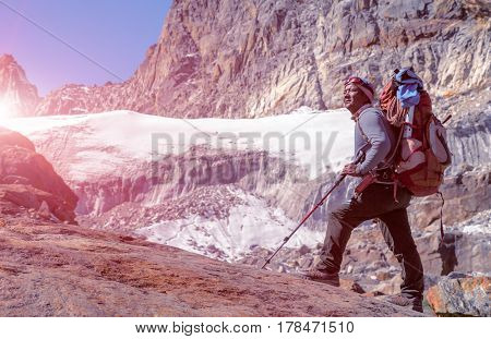 Toned Portrait of Nepalese professional Mountain Guide staying on Rock and looking up at high Altitude Summits and Glacier carrying Backpack with alpine climbing Gear shining Sun light on Background.