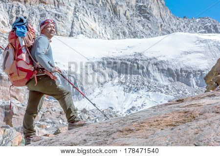 Nepalese professional Mountain Guide staying on Rock and looking up at high Altitude Summits and Glacier carrying Backpack with alpine climbing Gear Glacier and Wall view on Background. poster