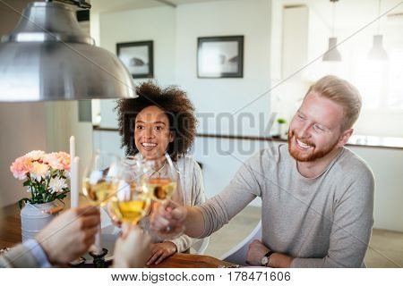 Happy friends enjoying a toast together at home.