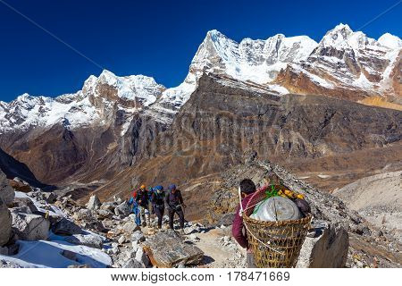 Group of Hikers and Nepalese Porter carrying many household and camping Items using traditional basket with head strap on popular touristic trek to high altitude Mountain. poster