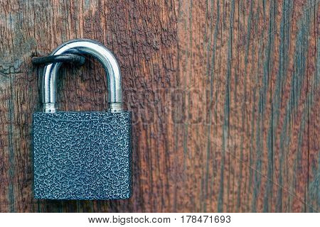 Padlock on the background of red wood