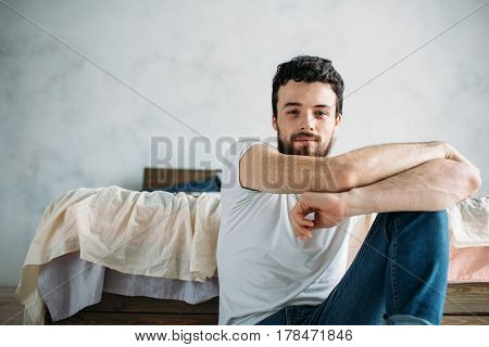 Young man sitting down on the floor near the bed. Attractive cute guy has folded his arms on knee and looking a camera. Close up