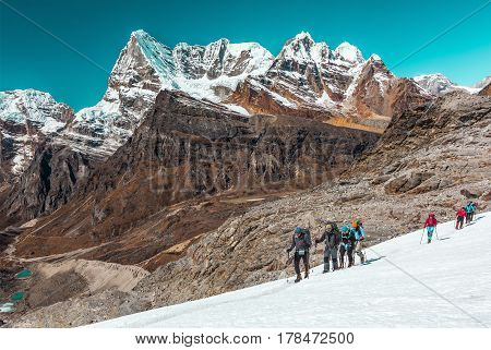 Group of Athletes of different Age and Ethnicity young and mature Caucasian and Asian moving across Glacier in high Altitude Mountains with Summits and Walls View on Background.
