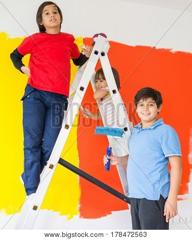 Children helping painting wall at home