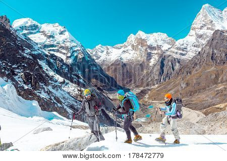 Group of People in sporty Outwear using climbing Gear traversing Glacier against Mountain Panorama with high Peaks and Valley Lakes