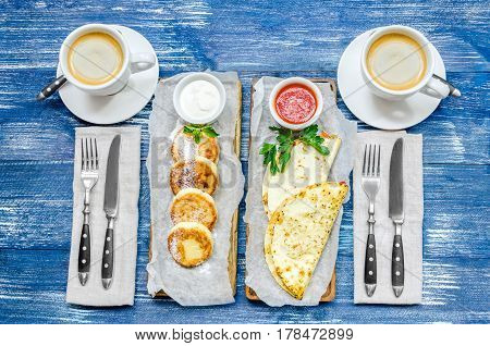 Breakfast for two - pancakes pita breads sauces coffee and cutlery on a blue denim background
