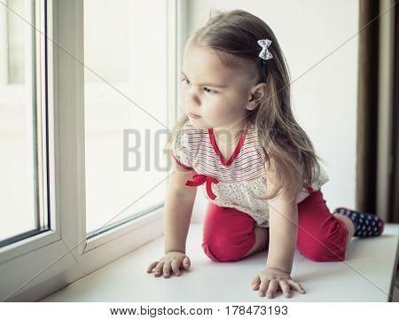 Little upset girl sitting on windowsill and looking through the window