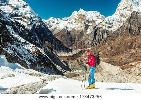 Mountain Climber using Cell Phone at high Altitude extreme Conditions on Glacier