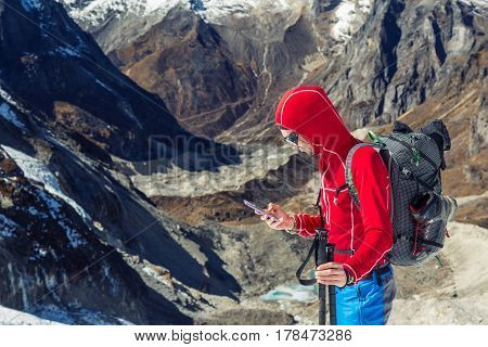 Alpine Climber in red Jacket and blue Pants using modern smart Phone in high Mountains calling to emergency service in extreme Conditions