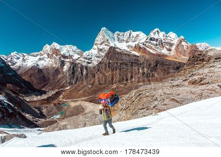 Nepalese Porter carrying traditional handmade Basket with luggage of mountain expedition using head strap on snowy glacier with majestic peaks on backgr