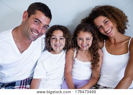 Portrait of family sitting together on bed at home