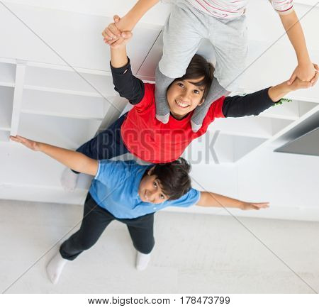 Cheerful funny children having fun and posing line up piggyback in new modern home top view
