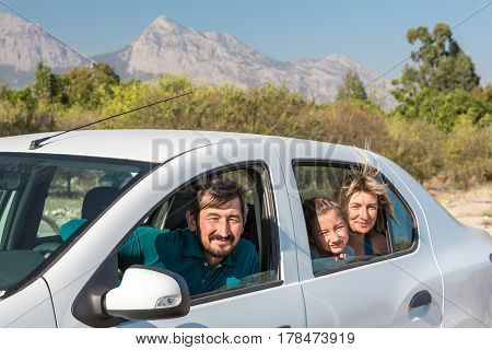 Family of three People Man Woman and Child travelling by Car smiling looking at Windows with Mountains and Garden on Background