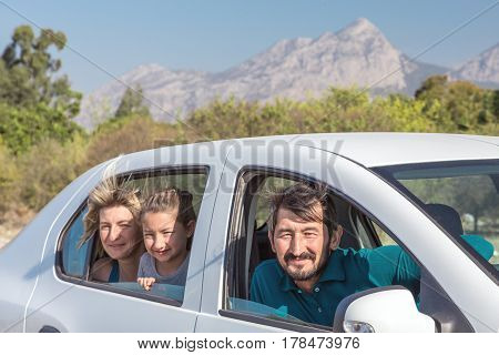Group of three People Man Woman and Child sitting in the Car excited and happy with Mountain View on Background