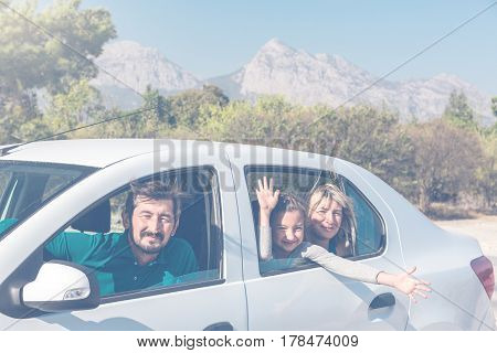 Family of three People Husband Wife and Child travelling on Vacation together by Car in non-urban country Landscape with Mountains and Forest