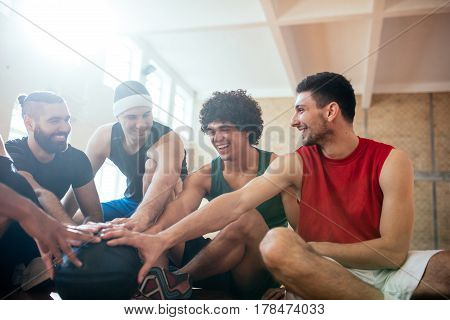 Shot of basketball teammates making a plan and holding a ball together while they're sitting on the floor indoors.