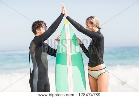 Couple holding a surfboard and giving a high five to each other on the beach