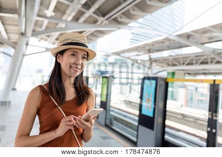 Woman use of mobile phone in train station