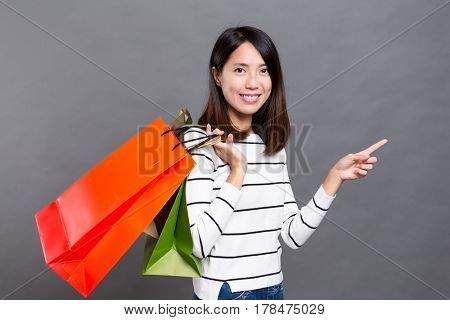 Asian young woman holding shopping bag and finger pointing up