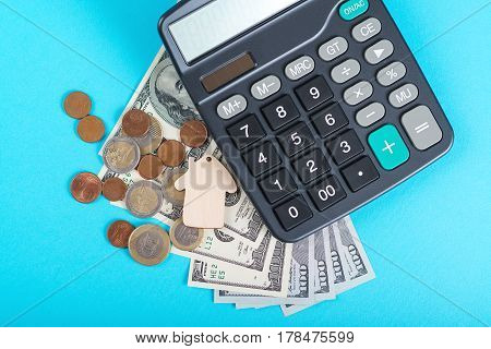 The concept of financial savings to buy a house. Model house dollars coins and calculator isolated on the blue background. Top view.