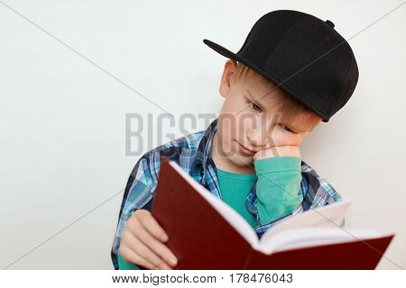 A photo of young schoolboy hard at work sitting with his hand on his cheek reading a book leraning new material preparing for the lessons. Young boy having tired expression while reading