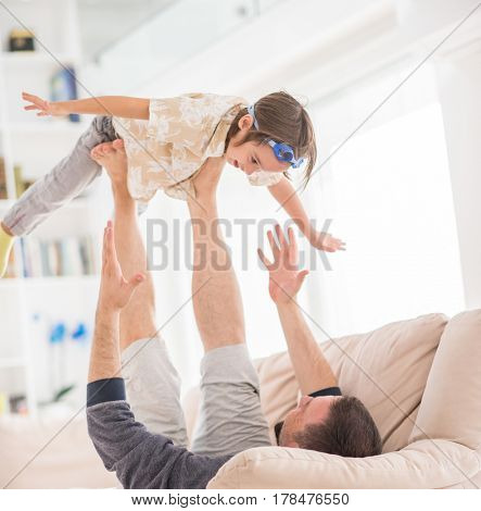 Father playing with his little son on sofa at home