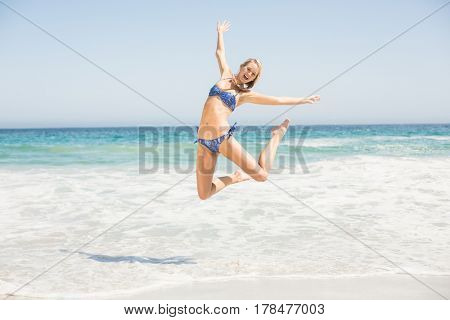 Carefree woman in bikini jumping on the beach with arms outstretch