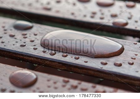 Water drops raindrops pattern on wooden table planks. Shallow depth of field.