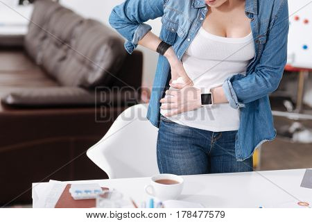 Lets examine it. Young woman wearing jeans and shirt standing behind her workplace while putting hands on the stomach