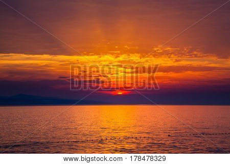 sunset with rays in clouds over the Adriatic sea