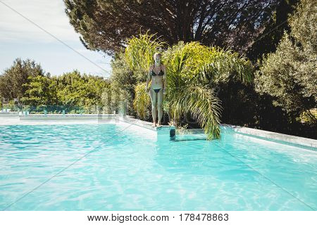 Fit woman standing on pools edge in a sunny day