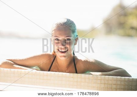 Portrait of smiling blonde in the pool leaning on edge