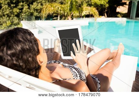 Fit brunette lying on deck chair and using tablet by the pool