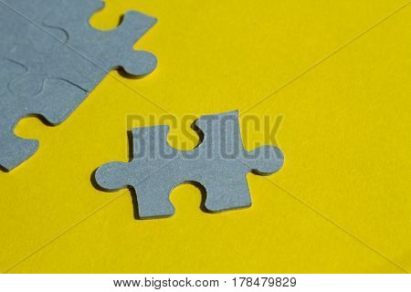 Jigsaw Puzzle pieces on yellow background horizontal view with copy space