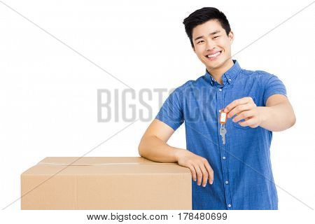Young man leaning on cardboard box and holding a key on white background