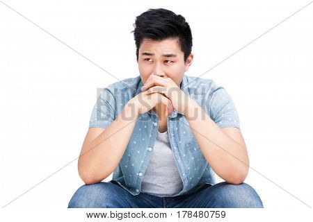 Young man looking worried on white background