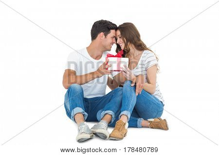 Happy couple receiving a gift on white background