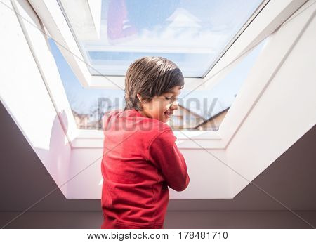 Kid on roof window in the room
