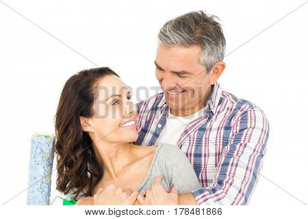 Portrait of couple holding roller on white background