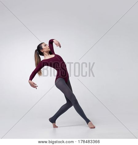 young beautiful woman dancer with long brown hair wearing maroon swimsuit posing on a light grey studio background