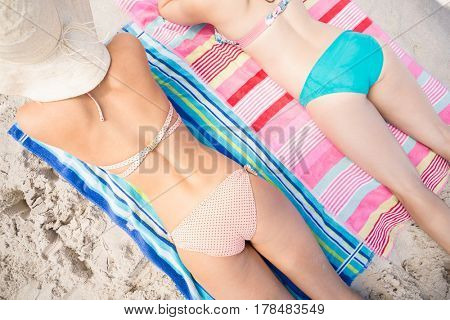 Two women in bikini lying on front at beach