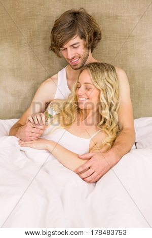 Cute couple cuddling in bed in the bedroom