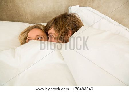 Cute couple cuddling under the blanket in their bed
