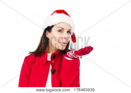 Beautiful brunette with santa hat blowing kiss on white background
