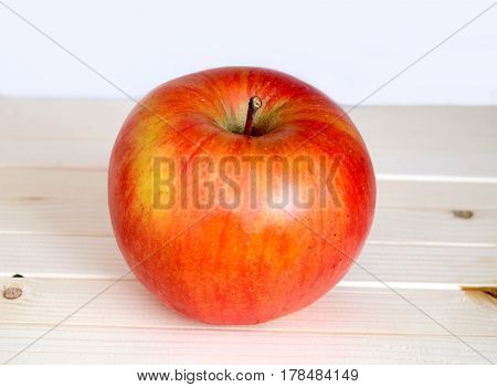 Big ripe red apple in beige wooden shelf on white background front view closeup