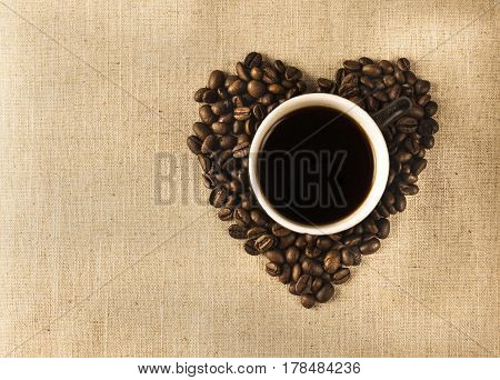 Cup with coffee and heart of coffee beanes on a linen background