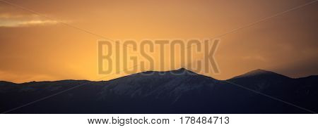 Majestic sunset/sunrise over dark mountains silhouettes