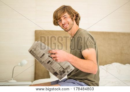 Handsome man reading a newspaper sitting on the edge of his bed