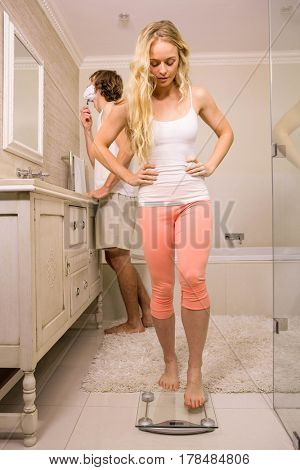Blonde woman about use a weighing scale while her boyfriend shaving at home