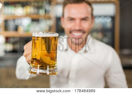 Handsome blurred man toasting in a bar